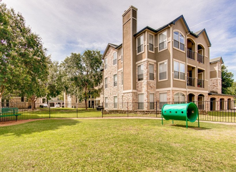 View of Dog Park, Showing Fenced-In Area, Bench, and Track at Stonebriar of Frisco Apartments